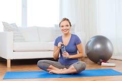 Mujer feliz con la botella de agua que ejercita en casa Imagen de archivo