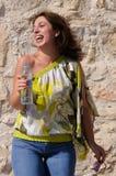 Mujer feliz con la botella de risa del agua. Imagen de archivo