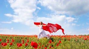 Mujer feliz con la bufanda roja en campo de la amapola Foto de archivo