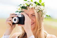 Mujer feliz con la cámara de la película en la guirnalda de flores Fotos de archivo libres de regalías