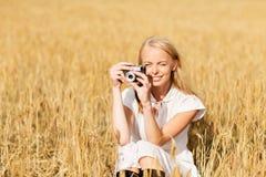 Mujer feliz con la cámara de la película en la guirnalda de flores Foto de archivo libre de regalías