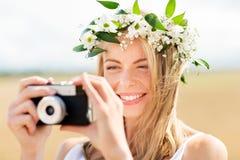 Mujer feliz con la cámara de la película en la guirnalda de flores Fotos de archivo