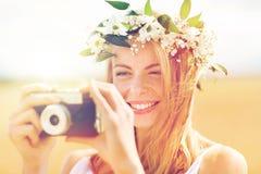 Mujer feliz con la cámara de la película en la guirnalda de flores Imagen de archivo libre de regalías