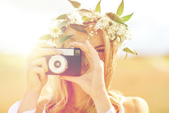 Mujer feliz con la cámara de la película en la guirnalda de flores Imagen de archivo
