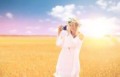 Mujer feliz con la cámara de la película en la guirnalda de flores Imagenes de archivo