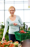 Mujer feliz con la cesta que elige las flores en tienda Fotos de archivo libres de regalías