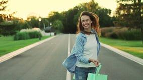 Mujer feliz con la compra en bolso que camina en parque de la ciudad Muchacha feliz metrajes