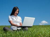 Mujer feliz con la computadora portátil en un prado Fotos de archivo libres de regalías