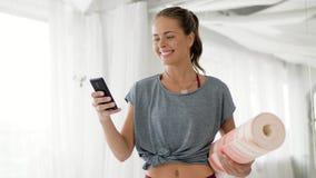 Mujer feliz con la estera del ejercicio en el estudio de la yoga almacen de video