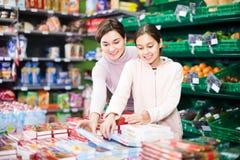 Mujer feliz con la hija que elige las galletas en supermercado Imagen de archivo libre de regalías