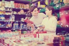 Mujer feliz con la hija que elige las galletas en supermercado Fotos de archivo