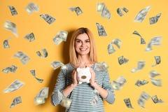 Mujer feliz con la hucha y el dinero que vuela imagen de archivo