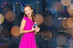 Mujer feliz con la magdalena del cumpleaños sobre ciudad de la noche Imágenes de archivo libres de regalías