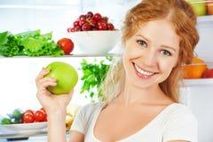 Mujer feliz con la manzana y el refrigerador abierto con las frutas, vegeta Foto de archivo