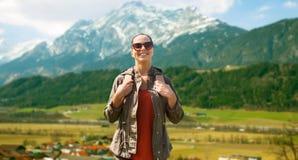 Mujer feliz con la mochila que viaja en montañas Fotografía de archivo