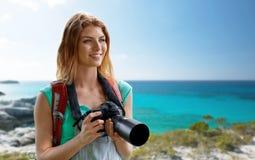 Mujer feliz con la mochila y cámara sobre la costa Foto de archivo