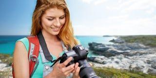 Mujer feliz con la mochila y cámara sobre la costa Imagen de archivo libre de regalías