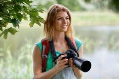 Mujer feliz con la mochila y la cámara al aire libre Foto de archivo