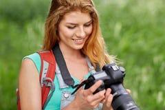 Mujer feliz con la mochila y la cámara al aire libre Imagenes de archivo