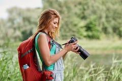 Mujer feliz con la mochila y la cámara al aire libre Imágenes de archivo libres de regalías