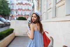 Mujer feliz con la mochila y los libros que camina en la ciudad Imágenes de archivo libres de regalías
