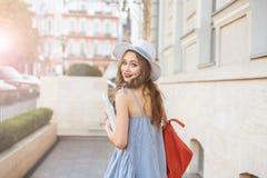 Mujer feliz con la mochila y los libros que camina en la ciudad Foto de archivo