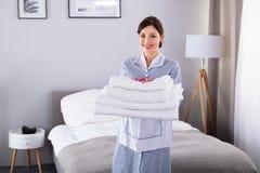 Mujer feliz con la pila de toallas blancas imagen de archivo libre de regalías