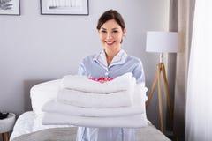 Mujer feliz con la pila de toallas blancas fotos de archivo libres de regalías