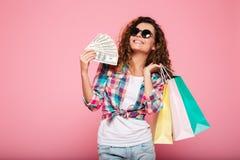 Mujer feliz con la presentación del dinero y de los panieres aislada Foto de archivo libre de regalías
