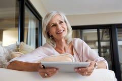 Mujer feliz con la tableta de la pantalla táctil en casa Imagen de archivo libre de regalías