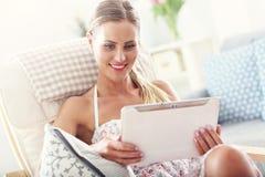 Mujer feliz con la tableta en casa Fotos de archivo