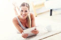 Mujer feliz con la tableta en casa Imagenes de archivo