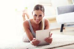 Mujer feliz con la tableta en casa Imagen de archivo libre de regalías