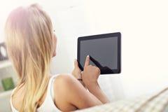 Mujer feliz con la tableta en el sofá Foto de archivo libre de regalías