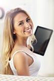 Mujer feliz con la tableta en el sofá Fotografía de archivo