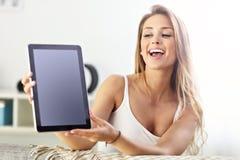 Mujer feliz con la tableta en el sofá Imagenes de archivo