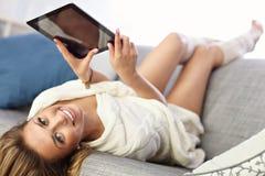Mujer feliz con la tableta en el sofá Fotografía de archivo libre de regalías