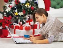 Mujer feliz con la tarjeta de crédito usando el ordenador portátil cerca del árbol de navidad Foto de archivo