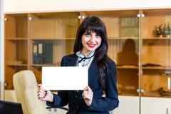 Mujer feliz con la tarjeta vacía en oficina Fotos de archivo