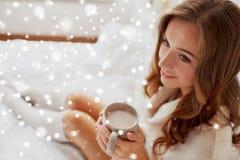 Mujer feliz con la taza de cacao en cama en casa Imagen de archivo libre de regalías