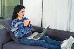 Mujer feliz con la taza de café caliente que pone en el sofá cómodo usando fotografía de archivo libre de regalías