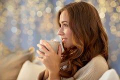Mujer feliz con la taza de café en cama en casa Imagen de archivo