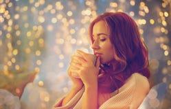 Mujer feliz con la taza de café en cama en casa Fotos de archivo