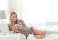 Mujer feliz con la taza de café en cama en casa foto de archivo libre de regalías