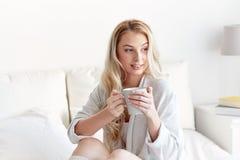 Mujer feliz con la taza de café en cama en casa Fotografía de archivo libre de regalías