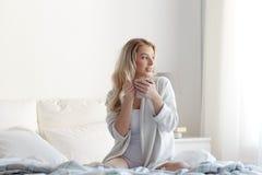Mujer feliz con la taza de café en cama en casa Fotos de archivo libres de regalías