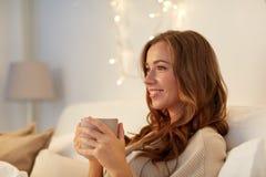 Mujer feliz con la taza de café en cama en casa Imágenes de archivo libres de regalías