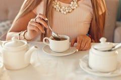 Mujer feliz con la taza de té Las manos sostienen una cucharilla Loza blanca en la etiqueta foto de archivo libre de regalías