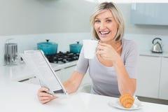 Mujer feliz con la taza y el periódico de café en cocina Foto de archivo