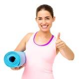 Mujer feliz con la yoga Mat Gesturing Thumbs Up foto de archivo libre de regalías